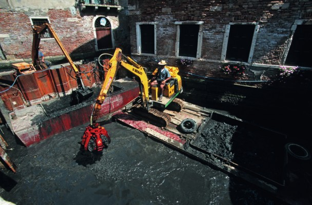 Rio dei Miracoli, June 1998.  The sludge is removed with hydraulic shovels and stored in bins, which are then loaded onto barges and taken to the dumping areas.